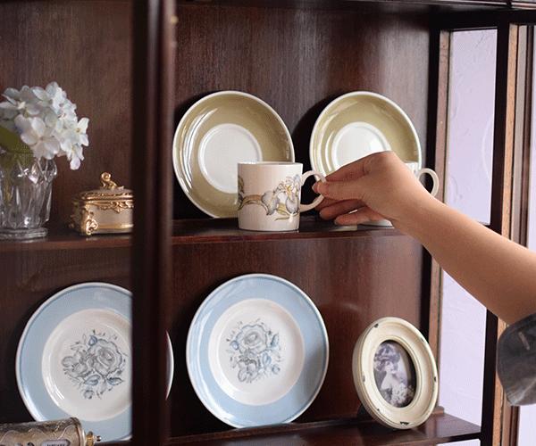 スージークーパーの陶磁器を濃い木の背板のキャビネットに飾る
