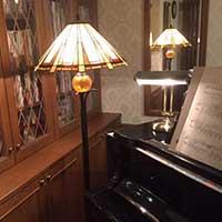 アンティーク風のスタンドライトとグランドピアノ